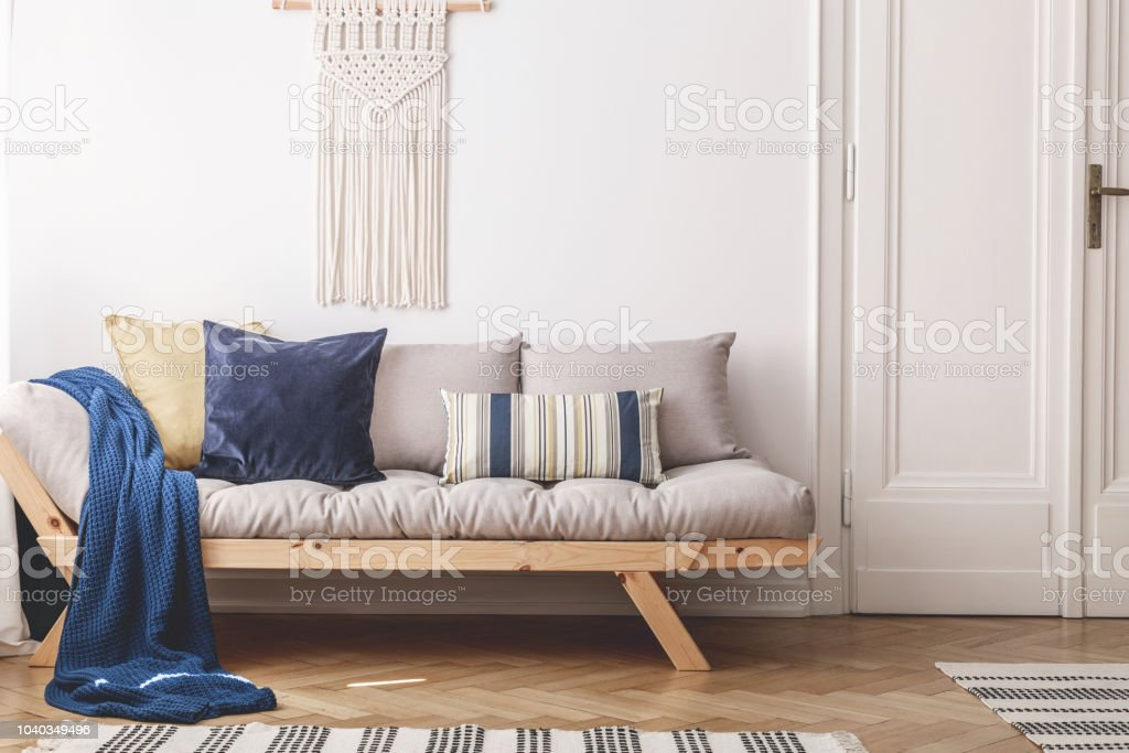 Blue Blanket And Cushions On Beige Wooden Sofa In White Loft Interior With Door Real Photo Stock Photo Download Image Now Istock