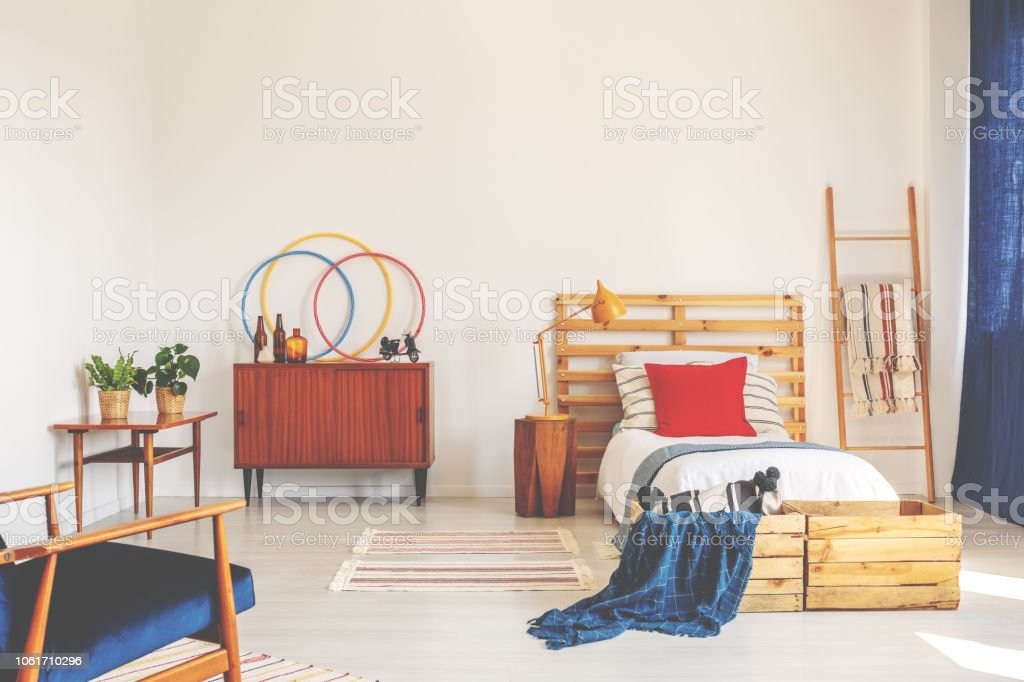 Blue blanket and red cushion on wooden bed in bedroom interior with cabinet and plants. Real photo stock photo