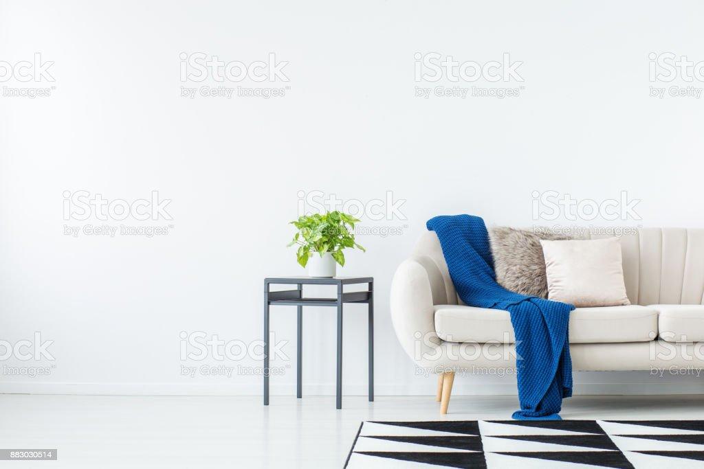Blaue Decke auf Beige sofa Lizenzfreies stock-foto