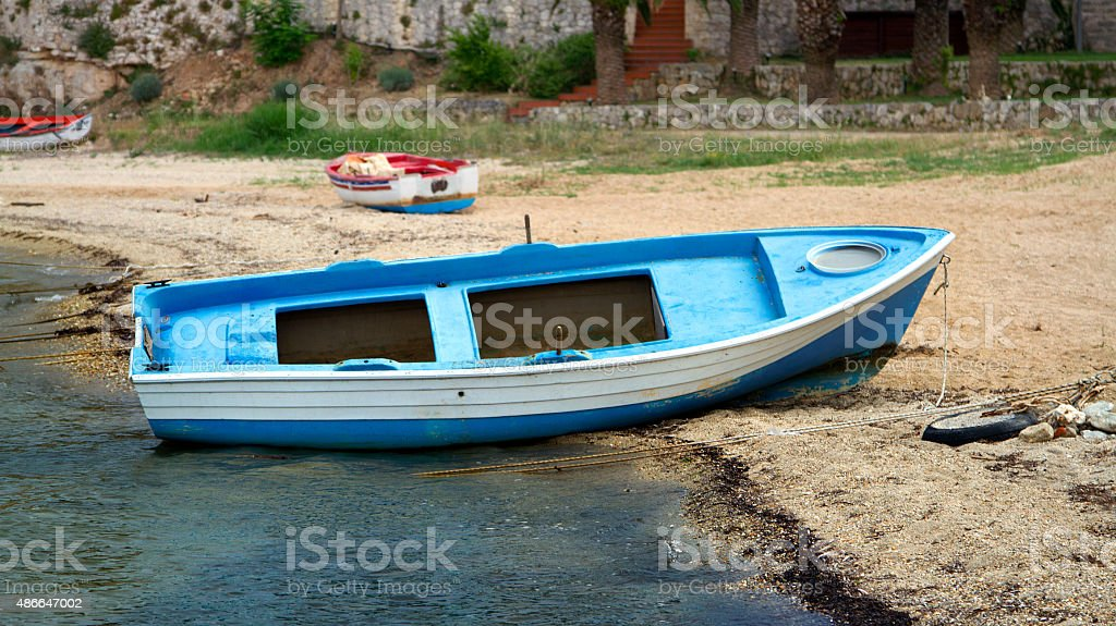 blue boat on shore stock photo