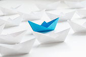 Blue paper boat among many white paper boats on white background.