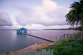Blue boat shed at sunset with still water and moving clouds