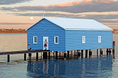 Perth, Australia – July 19, 2016: An unidentified photographer and model captured as the moon rises at  Crawley Edge Boatshed, a well-recognized and frequently photographed site in Perth. The boatshed is thought to have been constructed in the early 1930s and has since been refurbished.