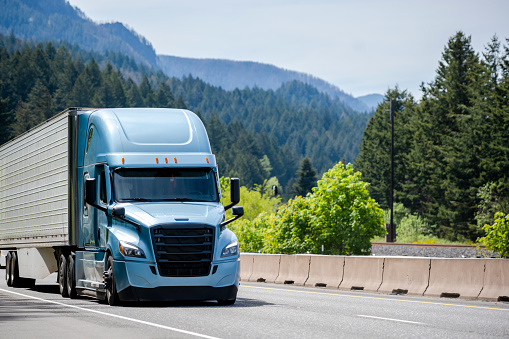 Blue big rig semi truck tractor with black grille transporting cargo in refrigerator semi trailer with reefer unit on the front wall running on the green forest highway road in Columbia Gorge