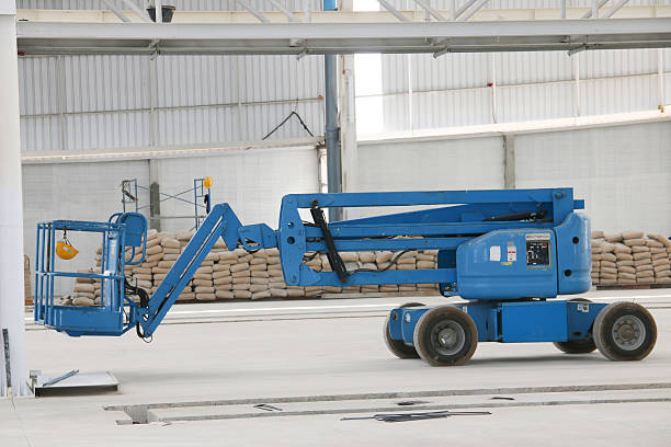 blue boom lift indoor The atmosphere indoor of heavy industrial plants. mobile crane stock pictures, royalty-free photos & images