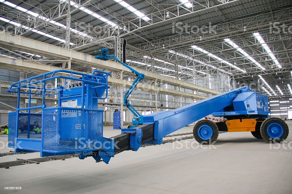 blue boom lift perspective indoor stock photo
