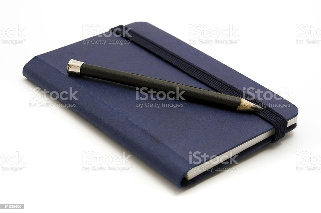 Blue bound notebook with pencil resting atop it stock photo
