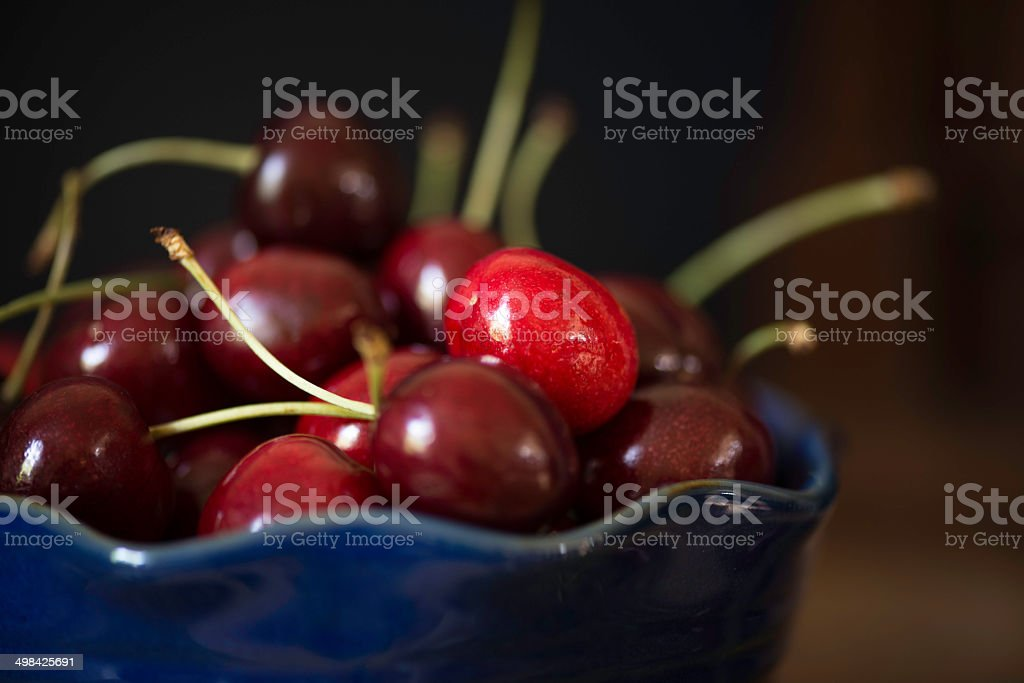 Blue Bowl of Cherries A blue bowl filled with cherries on a rustic wooden table. Blue Stock Photo