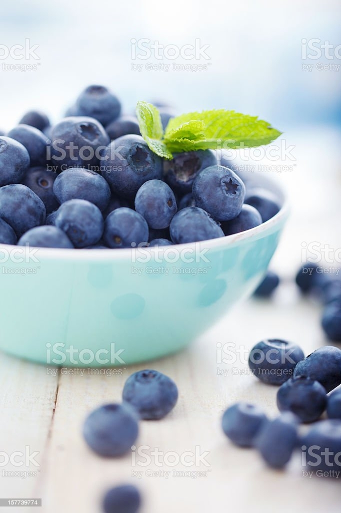A blue bowl overfilled with blueberries Blueberries in a bowl with leafs of mint Abundance Stock Photo