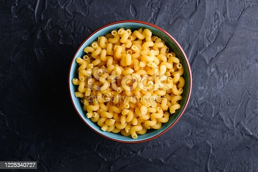 istock Blue bowl with cavatappi uncooked golden wheat curly pasta on textured dark black background, top view 1225340727