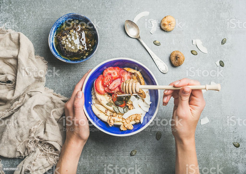 Blue bowl with healthy vegetarian breakfast ingredients in woman's stock photo