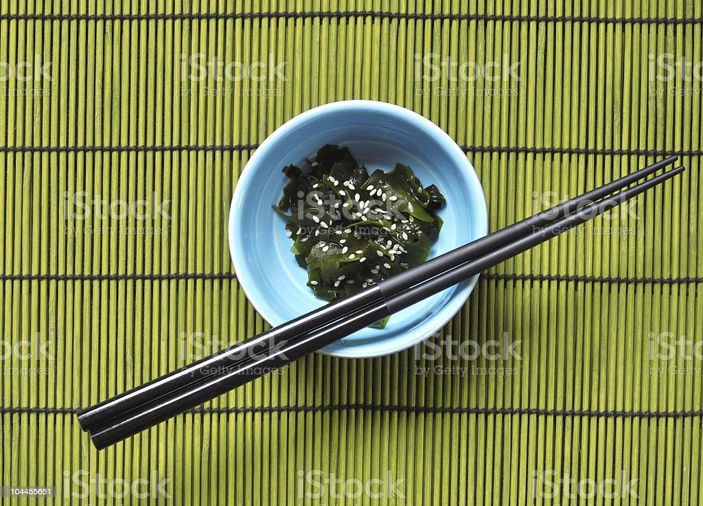 Blue bowl with Wakame and chopsticks stock photo