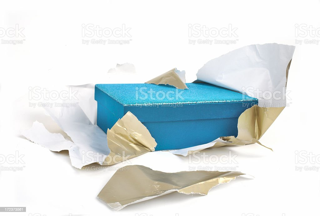 A blue box half unwrapped from gold paper stock photo