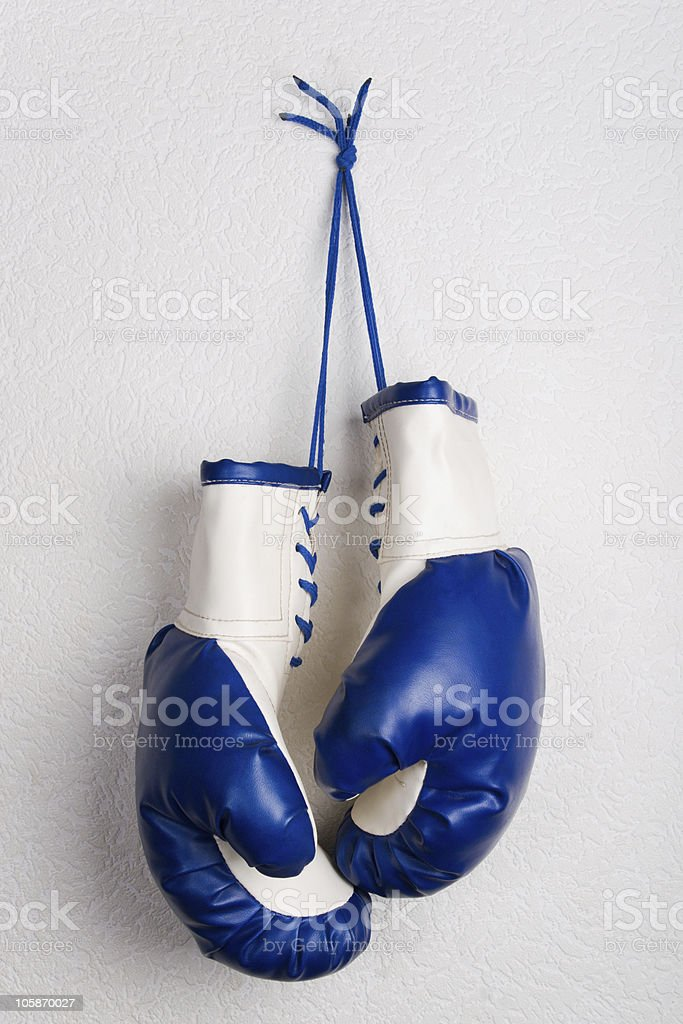 Blue boxing gloves handing on wall royalty-free stock photo