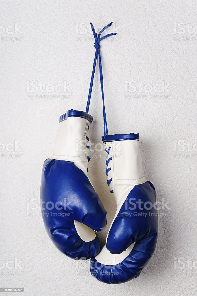 Blue boxing gloves on the wall stock photo