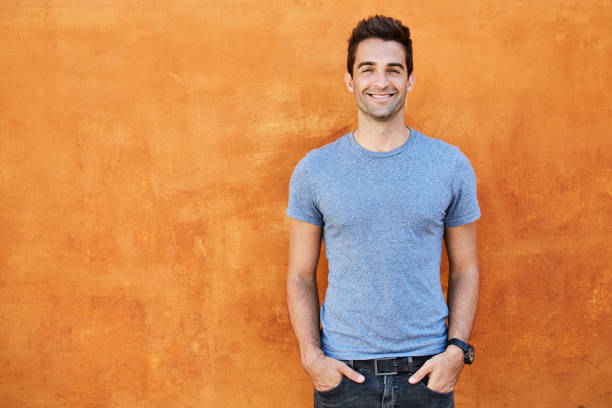 Blue boy on orange Guy in blue t-shirt against orange wall, smiling hands in pockets stock pictures, royalty-free photos & images