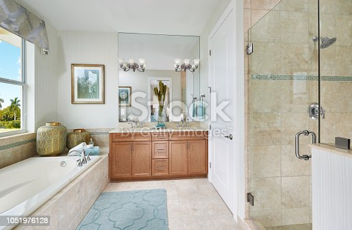 A beach like bathroom in a model home has a bath tub on the left hand side of the shot with two gold and blue pots of varying sizes on the far end of the tub. Soap, towels, and bubble bath are also provided in the same location. The tub has a view of the outdoors with a double pane window. The bathtub is white with sand colored tile around it. The walls are an eggshell white with an abstract picture of a dandelion in bloom on the far wall. Next to the picture is a large mirror with two light fixtures in the middle of it. Below is a vase with a plant in it, a double vanity, wash clothes, and light brown cabinetry with stainless steel handles. The floor is the same sand tile with a blue patterned rug. A white door leads into the next room, and beside the door, there is a glass shower with a darker sand tile. The accent for the shower is a blue stripe.