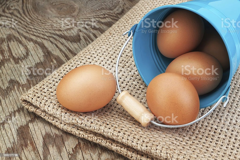 Blue bucket and easter eggs scattered on sackcloth. royalty-free stock photo