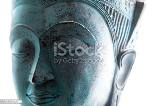 Blue Buddha face. Spiritual lifestyle close-up. Soft selective focus image of contemporary Buddhist head statue on white background. Serene expression of tranquility, meditation and mindful devotion.