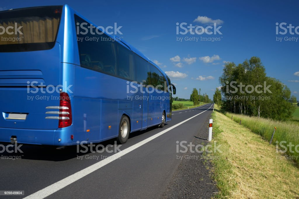 Blue bus traveling on asphalt road in a rural landscape stock photo