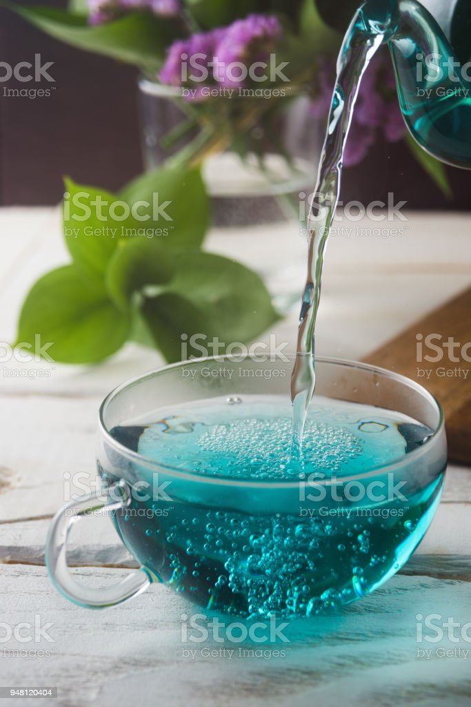 Blue Butterfly Pea tea poured in a glass cup, Clitoria Ternatea tea, selective focus, closeup stock photo