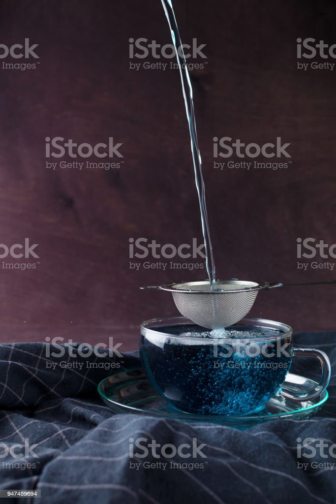 Blue Butterfly Pea tea poured in a glass cup on a dark stripped towel, Clitoria Ternatea tea, selective focus, dark background stock photo