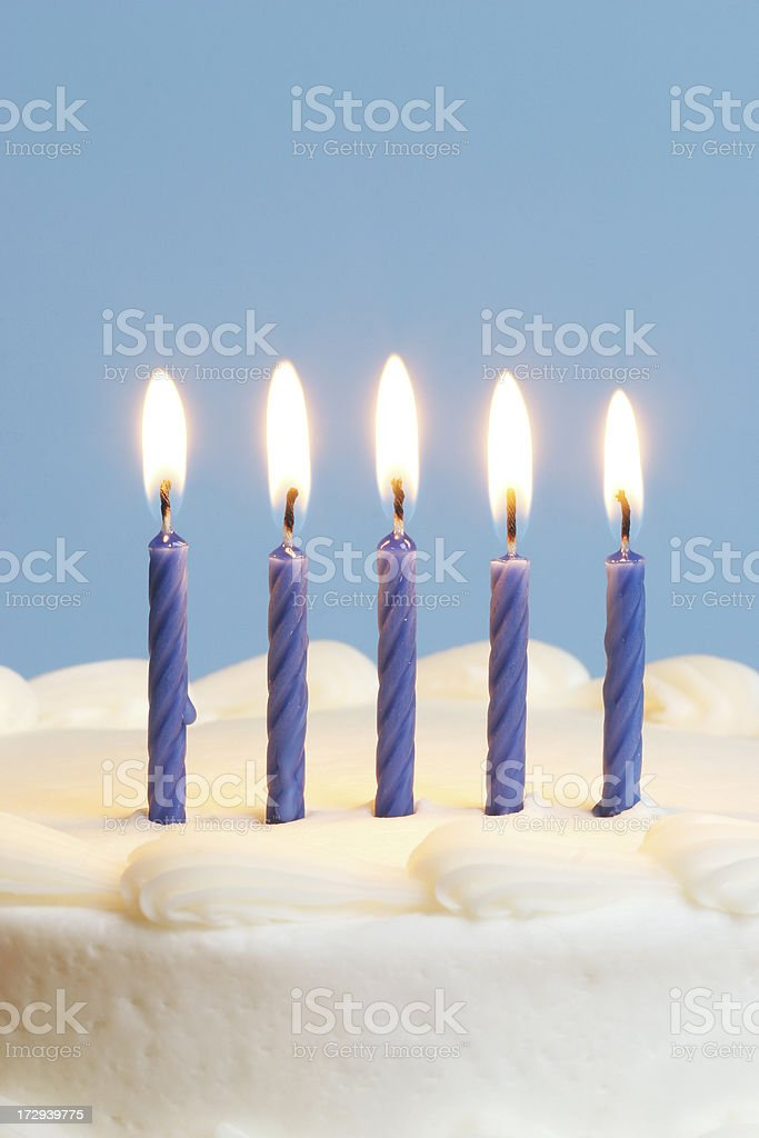 Blue candles on white cake stock photo