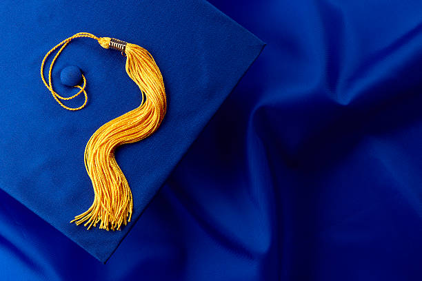 Blue Cap and Gown Blue mortarboard and yellow tassel shot on blue graduation gown, space for copy tassel stock pictures, royalty-free photos & images