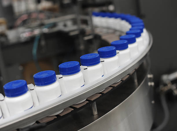 blue capped drug bottles on conveyor - pharmaceutical factory stock pictures, royalty-free photos & images