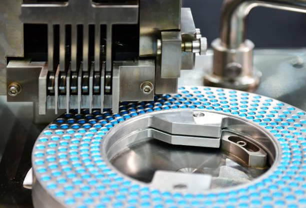 blue capsule medicine pill production line - farmaco foto e immagini stock
