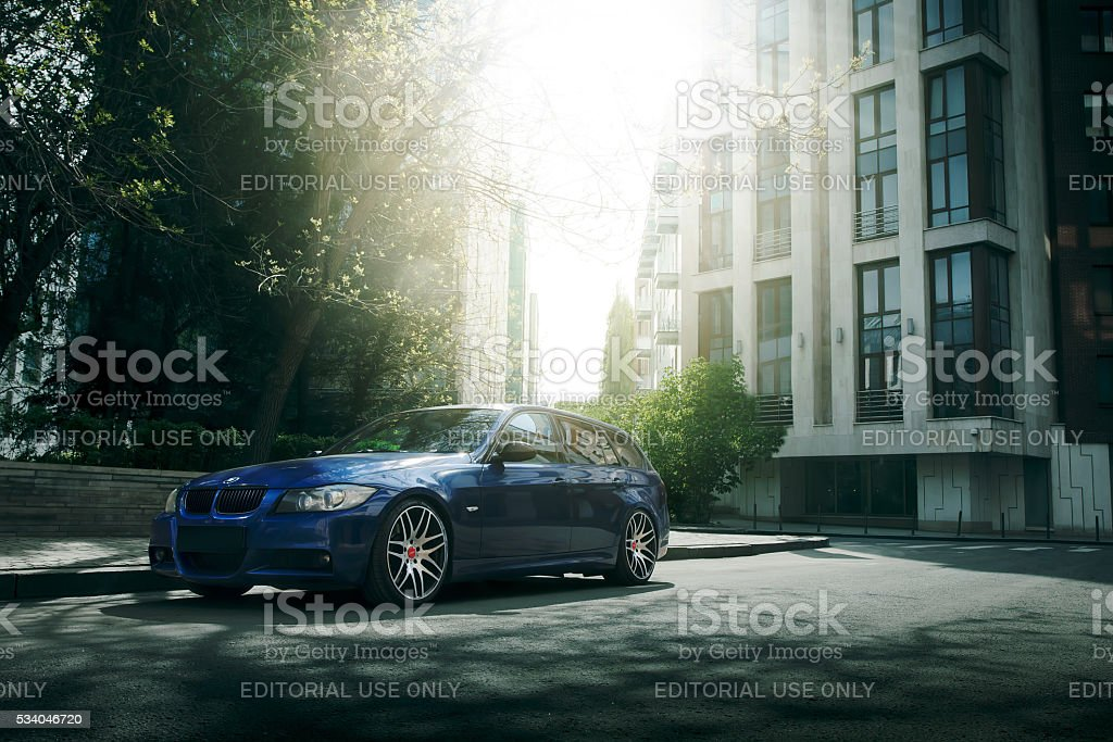Blue car BMW 5 series E90/E91 stay on asphalt road Moscow, Russia - May 10, 2015: Blue car BMW 5 series E90/E91 stay on asphalt road in the city Moscow at daytime Asphalt Stock Photo