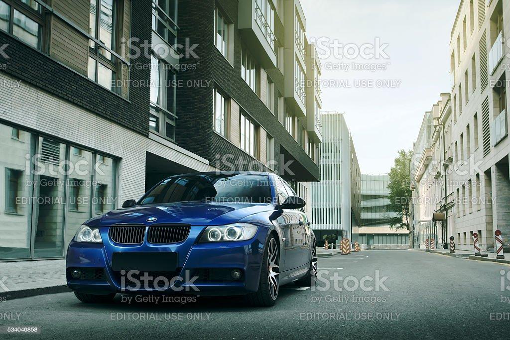 Blue car BMW 5 series E90/E91 stay on asphalt road