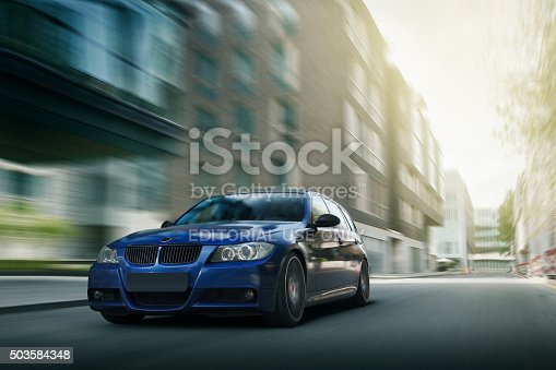 istock Blue car BMW E90 fast speed drive on city road 503584348