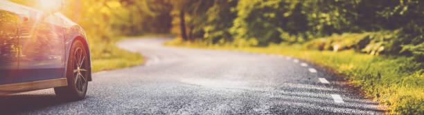 Blue car on asphalt road in summer stock photo
