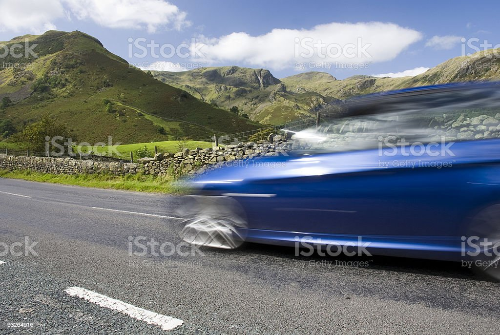 Blue car speeding, Lake District, UK stock photo