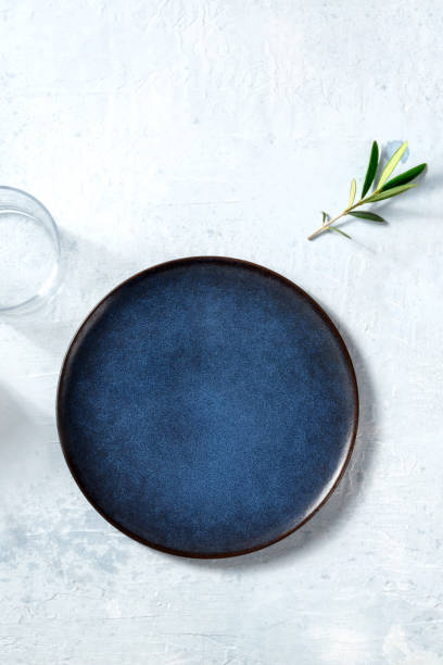 Blue ceramic plate, shot from the top with a glass and an olive branch stock photo