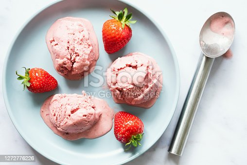 Three scoops of strawberry ice cream are sitting on a blue ceramic plate. There are fresh large red strawberries in between the scoops and and a used ice cream scoop is sat beside the plate.
