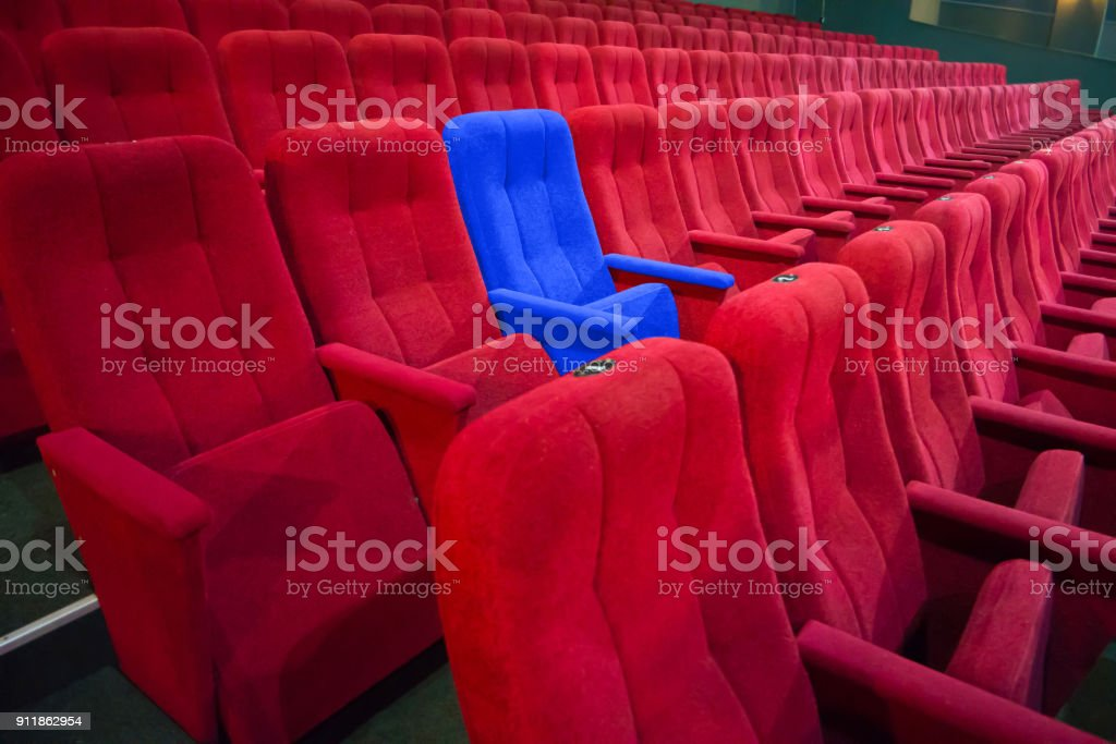 Blue chair between rows of red seats stock photo