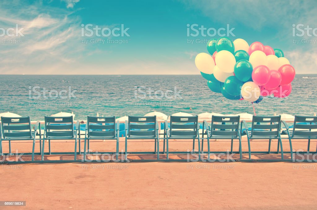 Blue chairs and balloons on the English Promenade in the city of Nice in France, vintage process stock photo