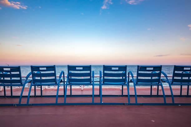 blaue stühle auf der promenade des anglais in nizza frankreich - nizza sehenswürdigkeiten stock-fotos und bilder
