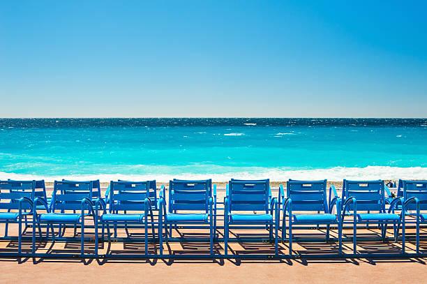 blue chairs on the promenade des anglais in nice, france - nizza sehenswürdigkeiten stock-fotos und bilder