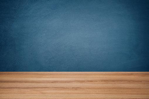 Empty school desk against blue chalkboard background