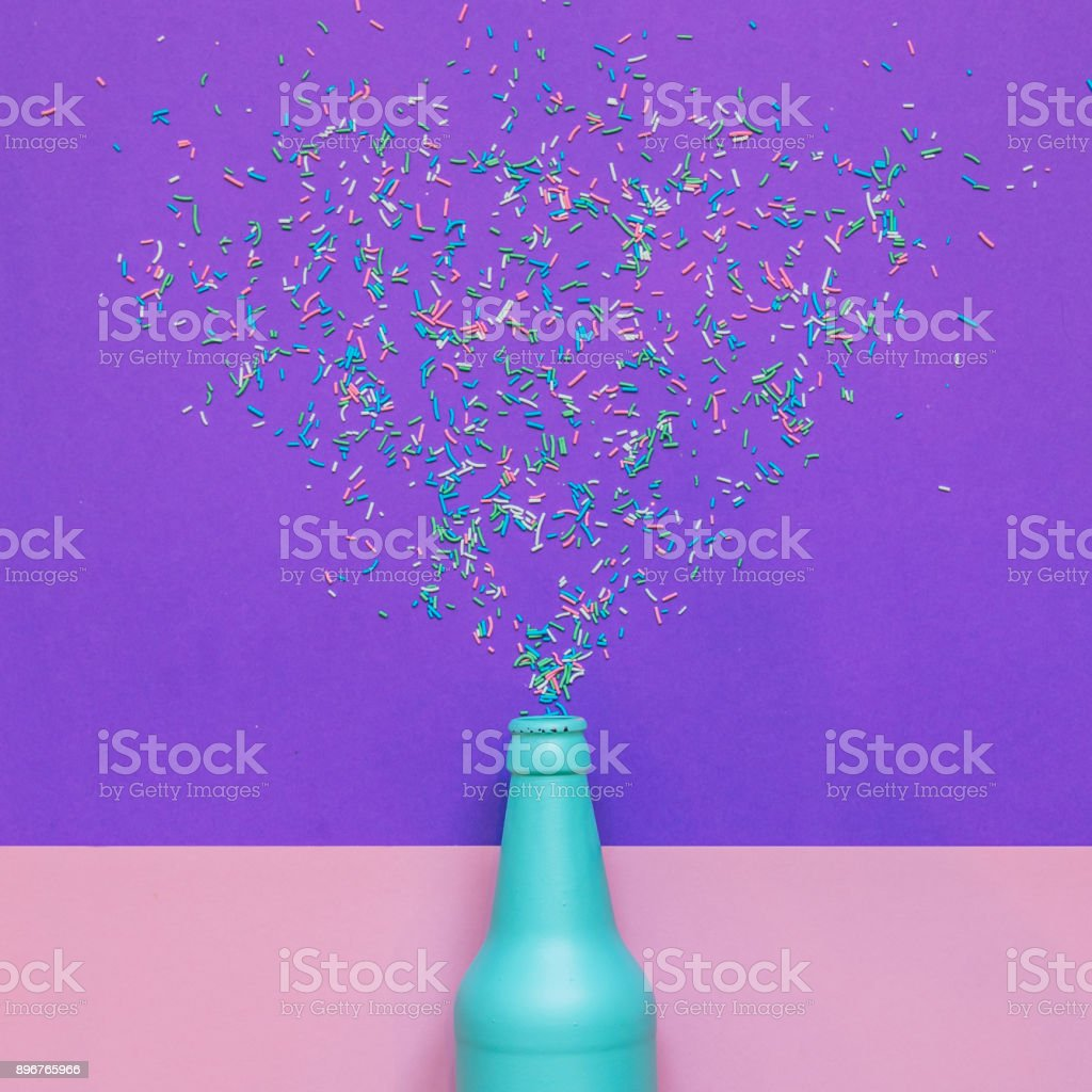 Blue champagne bottle with confetti glittering splashes. stock photo