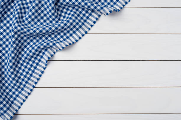 Blue checkered tablecloth on an old wooden table. Close up stock photo
