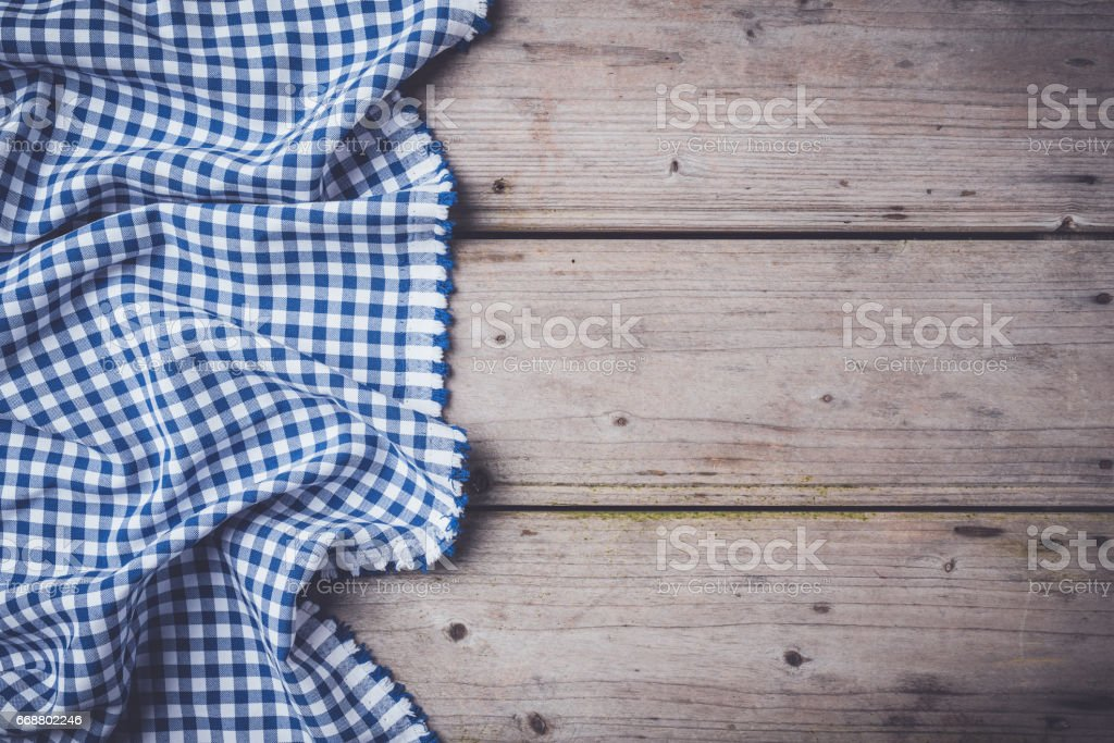 Blue checkered tablecloth on an old wooden table stock photo
