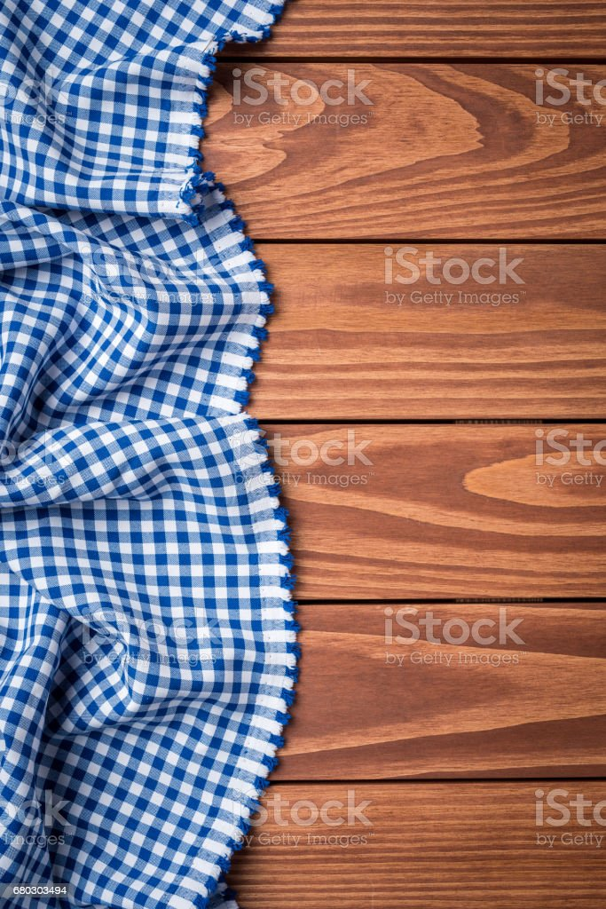 Blue checkered tablecloth on an old wooden table. stock photo