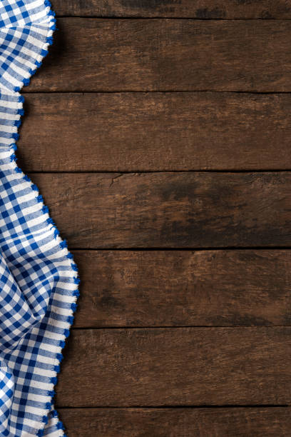 Blue checkered tablecloth on wooden background with copyspace stock photo