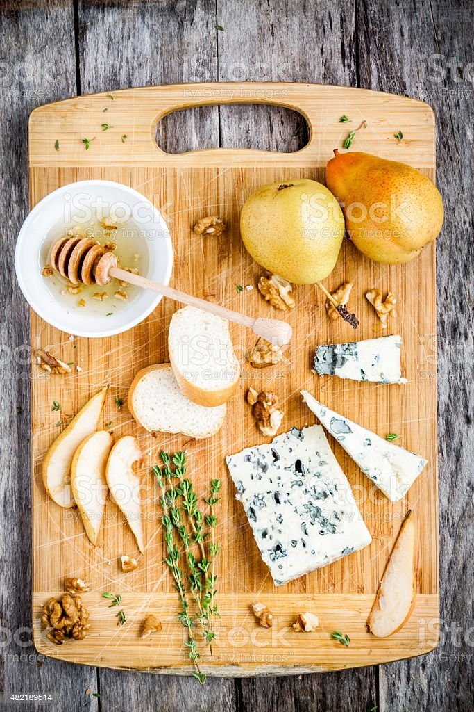 Blue cheese with pear, nuts and honey top view stock photo