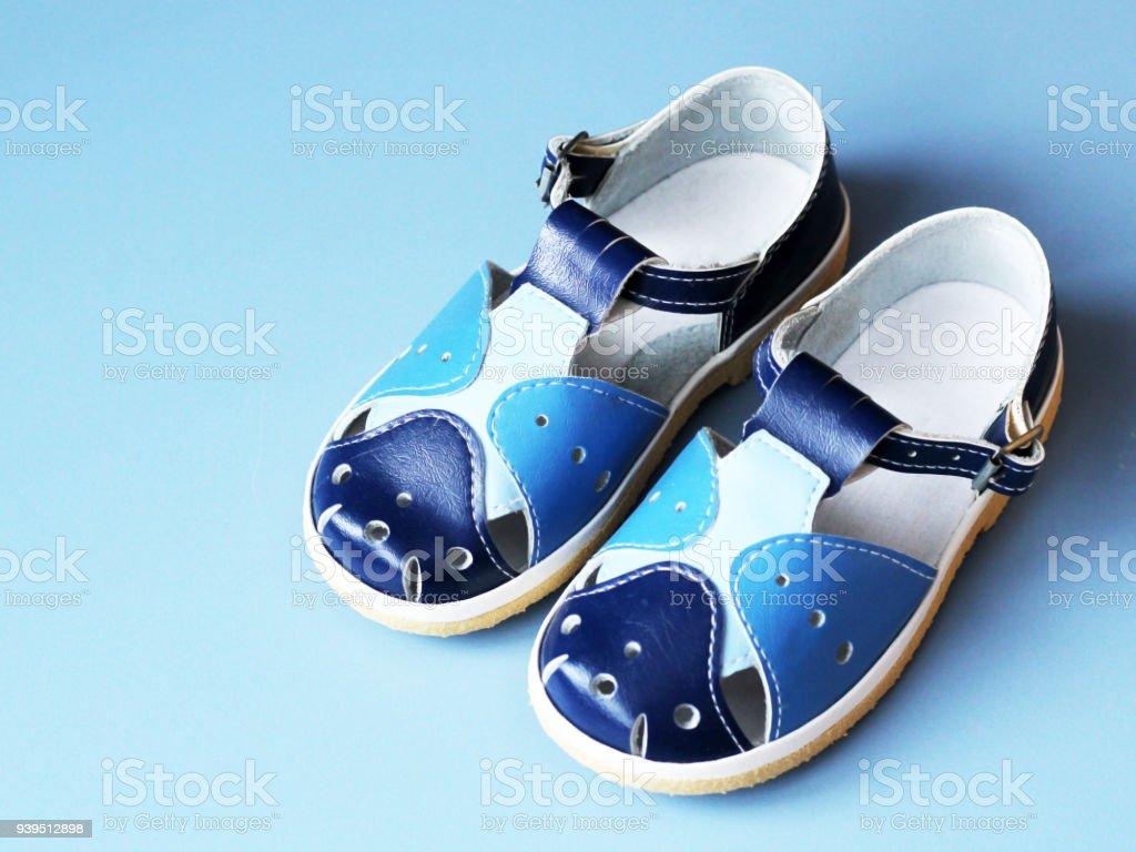 Azul sandálias da criança em fundo azul - foto de acervo