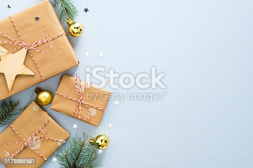Blue Christmas background with gifts box, fir tree branch, golden balls, handmade wooden Xmas decorations, glitter confetti stars. Christmas, winter, new year concept. Top view with copy space